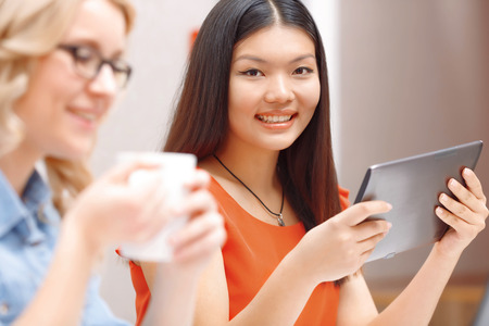 asian business: Multicultural team. Smart Asian woman smiling working using tablet and her blond colleague holding a cup of tea Stock Photo