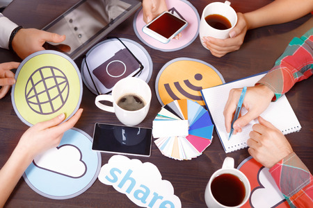 cup four: Creative process. Hands of four people holding cup smartphone tablet icon and writing notes in a notebook on the table with pallet