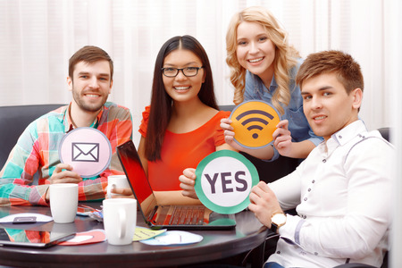 developers: Creative team. Young app developers sitting at the table with laptop and other devises  working on the project smiling and showing yes message wifi  icons Stock Photo