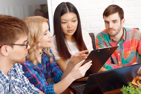 discussion: Discussion of a project. Team of app developers discussing the project looking at the tablet and smiling Stock Photo