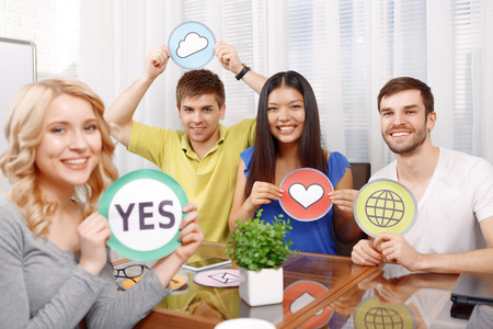 hilarious: Hilarious work. Blond girl and her team showing yes cloud heart and internet icons smiling sitting in the light room