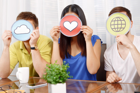 heart work: Hilarious work. Three young app developers hiding behind cloud heart and internet icons sitting at the table in a light room Stock Photo