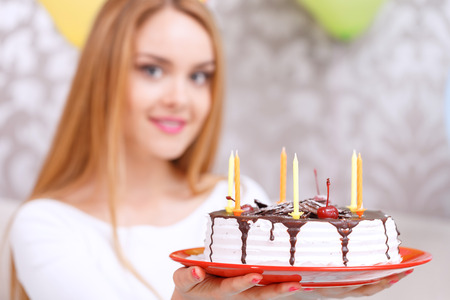 Portrait of a young beautiful blond girl holding a birthday cake with candles on a red plate smiling celebrating in a decorated room photo
