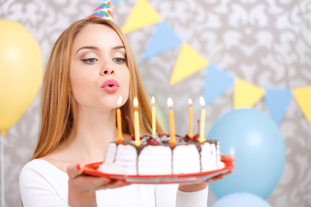 Portrait of a young beautiful blond girl wearing cone cap holding a red plate with birthday cake and blowing candles making a wish