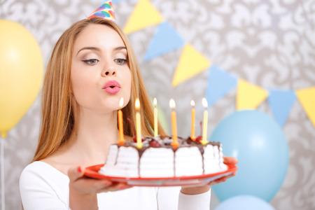 pastel de cumplea�os: Retrato de una joven y bella chica rubia llevaba gorra de cono que sostiene una placa roja con la torta de cumplea�os y soplando velas pidiendo un deseo Foto de archivo