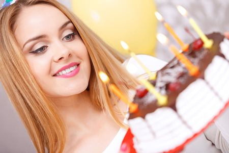 Portrait of a young beautiful blond girl wearing cone cap looking at birthday cake covered with chocolate with candles in the light decorated room photo