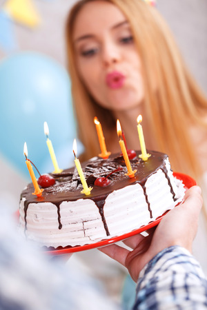 cone cake cone: Make a wish. Young beautiful blond girl wearing cone cap blowing candles from her birthday cake making a wish