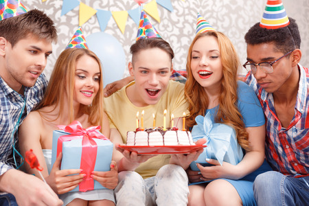 Celebration. Young happy boy blowing candles from his birthday cake making a wish while his friends smiling and holding presents in their hands and looking at the cake photo