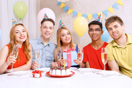 Birthday party. Young happy people wearing cone caps sitting at the table holding glass of champagne, present while the cake standing on the table in a decorated with balloons room photo