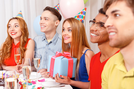 cone cake cone: Birthday party. Young happy people wearing cone caps sitting in a row at the table holding glass of champagne, present while the cake standing on the table in a decorated with balloons room Stock Photo