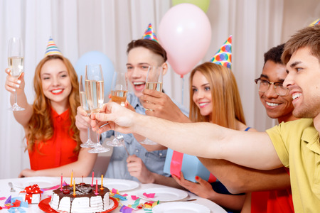 Birthday party. Young happy people wearing cone caps sitting at the table laughing holding and clinking glasses of champagne near the birthday cake photo