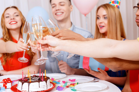 cone cake cone: Birthday party. Young happy people wearing cone caps sitting at the table laughing holding and clinking glasses of champagne near the birthday cake Stock Photo