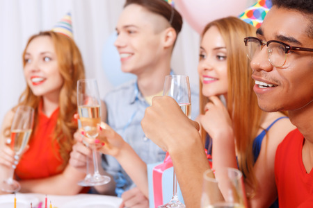 Birthday party. Young happy people wearing cone caps sitting in a row at the table holding glass of champagne, present while the cake standing on the table in a decorated with balloons room photo