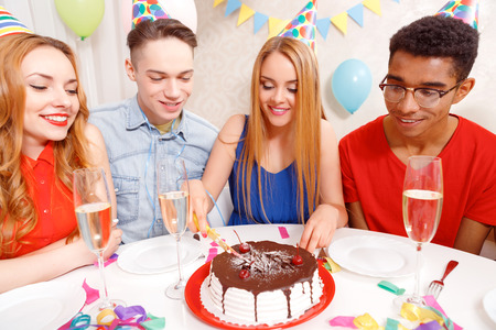 cone cake cone: Birthday party. Young beautiful blond girl wearing cone cap cutting a birthday cake into pieces while her friends waiting and looking at it with appetite Stock Photo