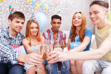 Celebration. The company of happy friends wearing cone caps clinking glasses of champagne to celebrating a birthday while boy holding a cake photo