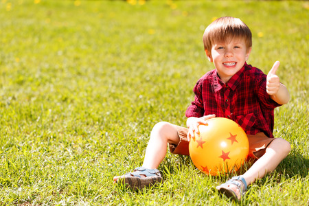 rubber ball: Giving thumbs up. Little cute smiling little boy sitting on grass, holding rubber ball and giving thumbs-up.