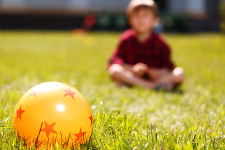 rubber ball: Round friend. Yellow rubber ball with stars on it lying on green grass o background of sitting little boy. Stock Photo