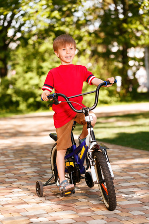 heals: Adventure time. Portrait of little smiling boy riding bike in park. Stock Photo