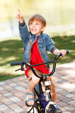 Little cute smiling boy riding bicycle in park and pointing upwards with his index finger. photo