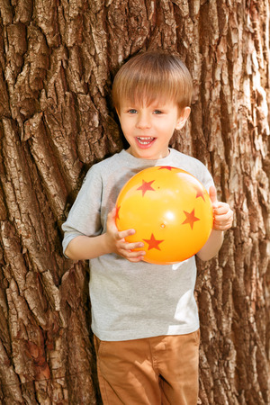 rubber ball: Going to throw. Laughing little boy standing in front of tree and holding rubber ball