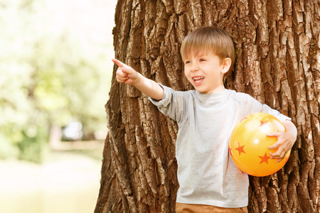 rubber ball: What is it. Smiling little boy standing in front of tree with rubber ball and pointing upwards. Stock Photo
