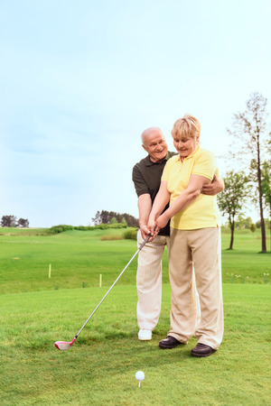 old man standing: Teaching with love. Old man standing on course behind his wife and teaching her to play golf Stock Photo
