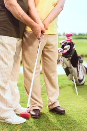 Doing careful. Close up of old man teaching elder woman to play golf on course. photo