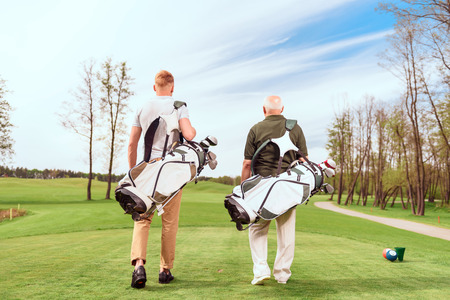 golfer: Father and son. Back view of old and young golf players walking on course with golf equipment.