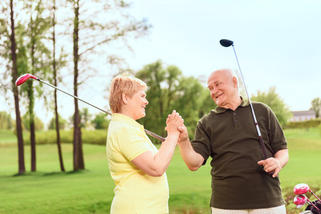 One team. Smiling senior man and woman standing on course holding golf clubs and their hands together photo