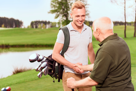 old and young: Nice job. Young and old golf players standing on golf course with golf equipment and shaking hands.