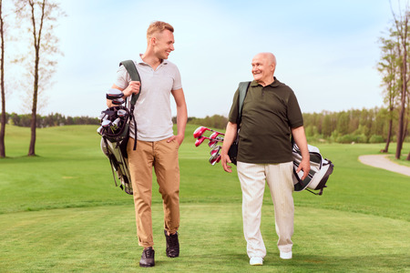 two generations: Two generations. Senior and young golf players walking through course with golf equipment.