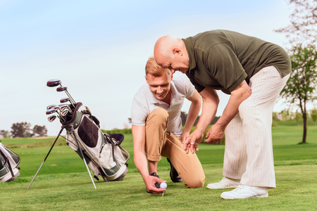 green man: Preparatory work. Young and old goler  putting ball on tee on course on background of bag.