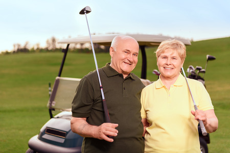woman golf: Satisfied with game. Two lovely senior people standing with golf clubs on background of cart on course. Stock Photo