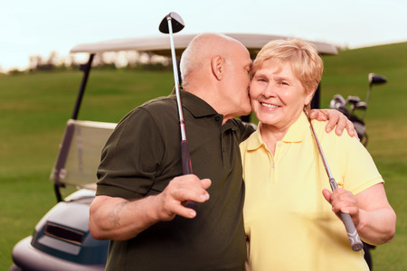 Showing love. Senior man with golf club giving kiss on cheek to his wife on background of cart on course. photo