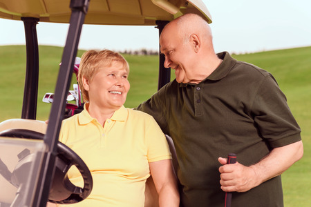Soft glance. Smiling senior man with golf club standing near his wife sitting in cart and gently hugging her. photo