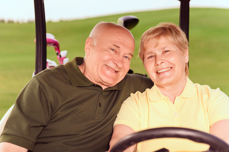 To next hole. Portrait of senior man and woman driving in cart on course. photo