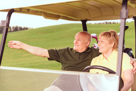 Look there. Senior smiling man and woman driving in cart on course, man pointing aside with help of his hand. photo