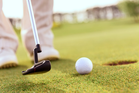 putt: Striking it gently Close up of man going to putt ball into hole with help of golf club Stock Photo