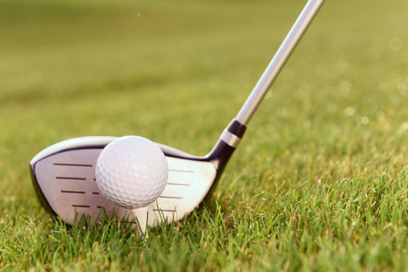 golf man: Typical combination. Close up of golf club and ball on tee put together on grass.
