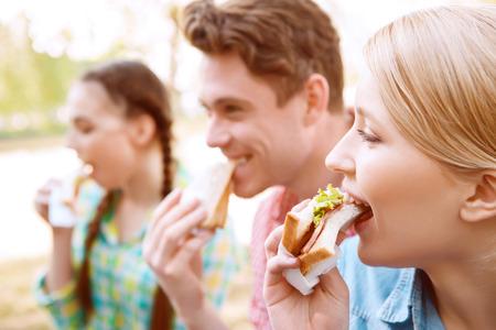 Abbeißen. Gruppe junge Leute, während sitzt auf Picknickdecke und essen Sandwiches