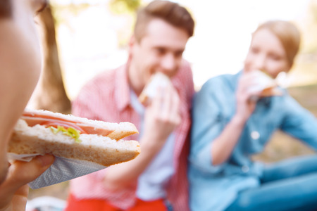 eating up: First bite.  Close up of young girl eating sandwich on background of another people during picnic