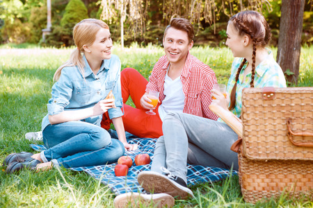 cover girls: Perfect time. Two pretty girls and handsome guy sitting on blue cover with glasses of soda and sandwiches during picnic.