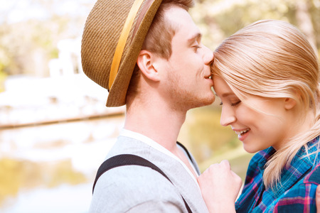 beso: Dulce beso. Apuesto joven de pie en el parque cerca del lago y besando a su novia en la frente