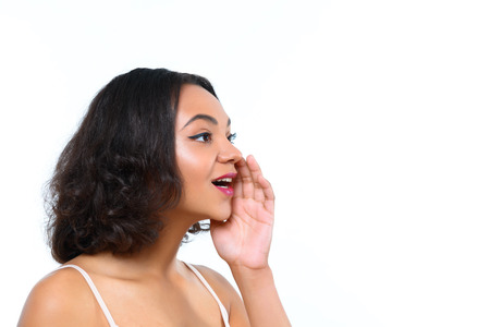 rumors: Spreading rumors. Pretty youthful mulatto woman gossiping with hand near her mouth on isolated white background. Stock Photo
