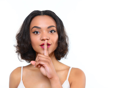 mulatto woman: Dont blab out. Attractive young mulatto woman standing with index finger on her mouth on white isolated background.