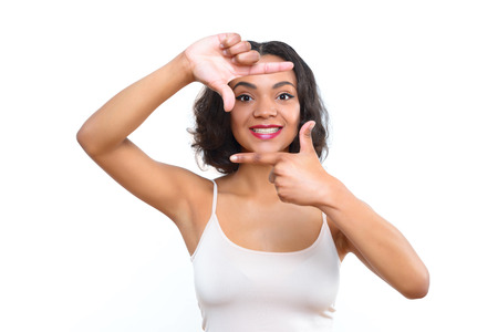 behind the scenes: Behind scenes. Smiling young mulatto lady showing with her fingers like she is in frame on white isolated background.