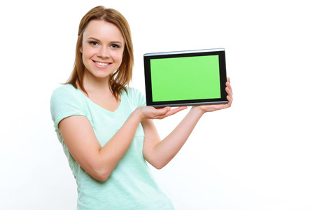 arms behind head: Look what I have. Young pretty smiling woman holding tablet in her hands on white isolated background. Stock Photo