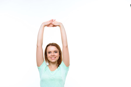 arms behind head: Morning gymnastic. Portrait of young smiling lady with holding arms above her body on white isolated background. Stock Photo
