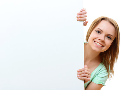 i am here: Here I am. Portrait of smiling young lady emerging from behind corner on white isolated background.