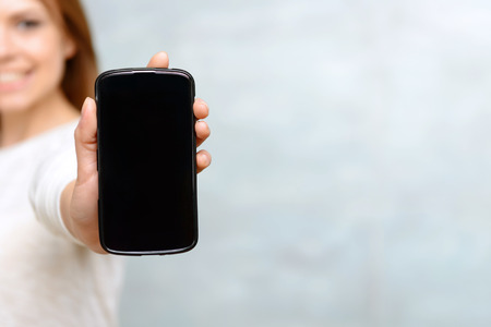 Close up of mobile phone showed by young smiling woman on isolated background. 写真素材